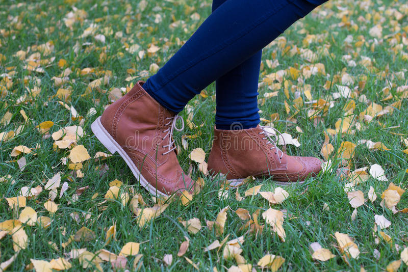 Women`s shoes on the background of grass and autumn leaves royalty free stock photo