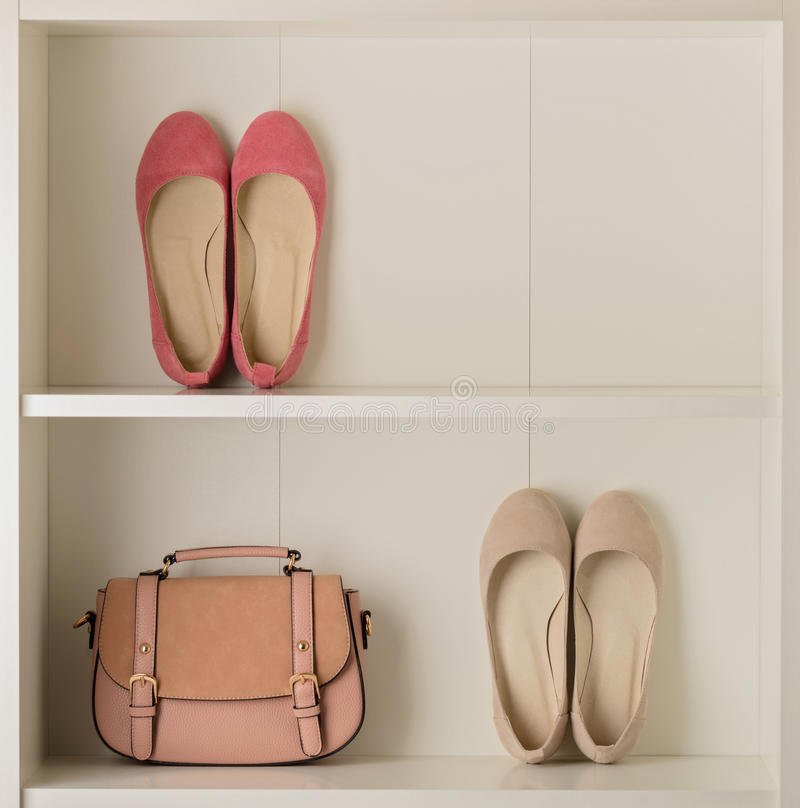 Women`s shoes ballet shoes and bag in the white wardrobe. Selective focus royalty free stock photo