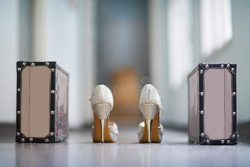 Women`s shoes with fine stud and with glitter. And two suitcases beside it royalty free stock photo