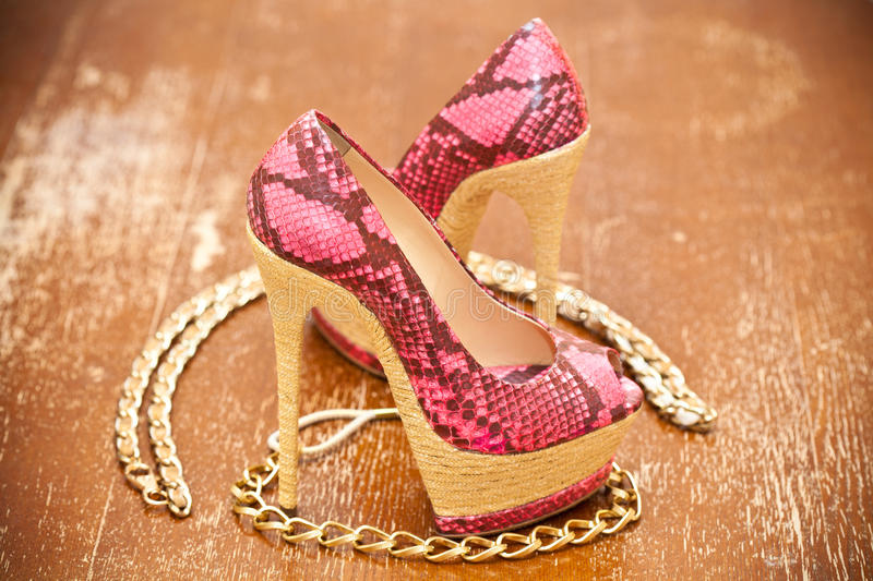 Women's shoes pink and gold chain. Stylized snake skin. Vintage style stock photo