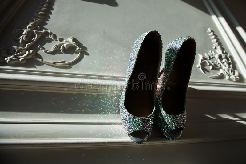 Women`s shoes with rhinestones on the panel. Women`s silver-colored shoes with multi-color rhinestones and highlights on the carved panel royalty free stock photos