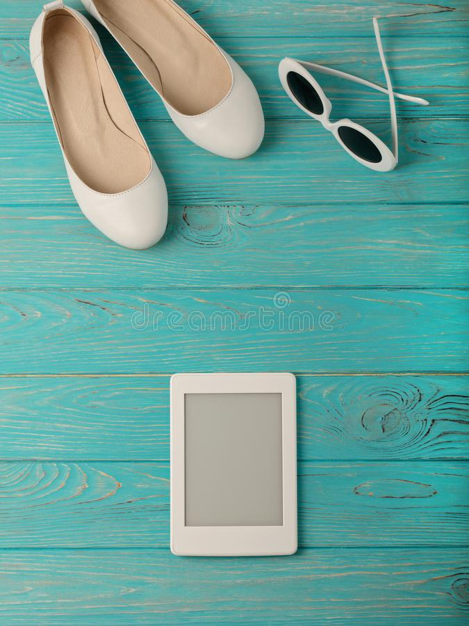 Women`s shoes and sun glasses white color, electronic book on a stock photography