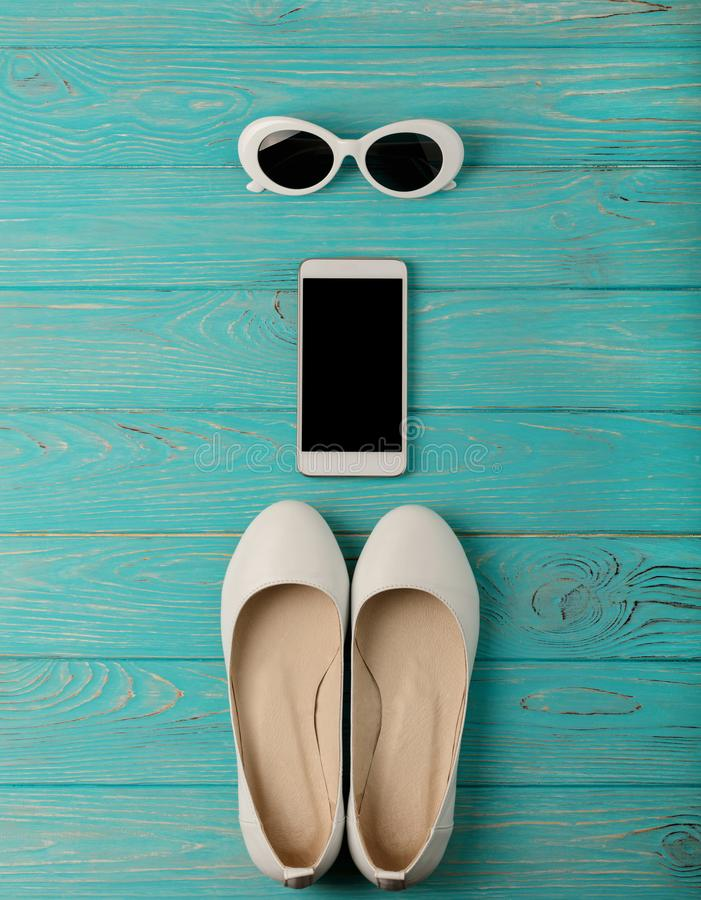 Women`s shoes and sun glasses white color, smartphone on a blue stock images