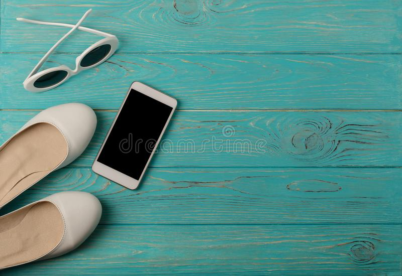 Women`s shoes and sun glasses white color, smartphone on a blue stock photo