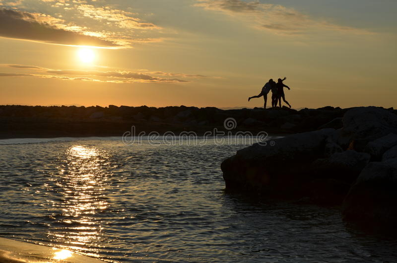 Women's silhouettes by sunrise at sea royalty free stock photography