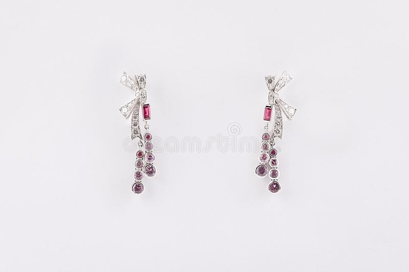 Women`s silver earrings in the form of a bow with light purple and purple stones, isolated on a white background. stock image