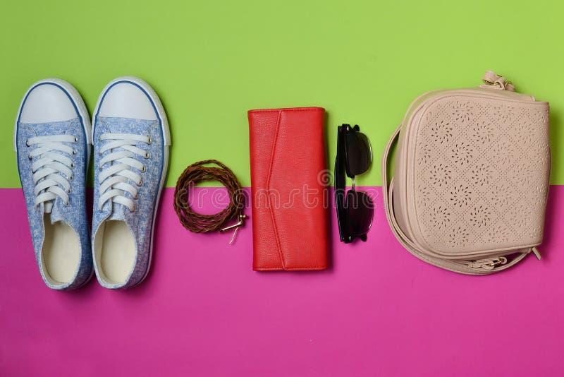 Women& x27; s-skor och modetillbehör på en grön rosa pastellfärgad bakgrund Gymnastikskor påse, handväska, bälte, solglasögon arkivfoto