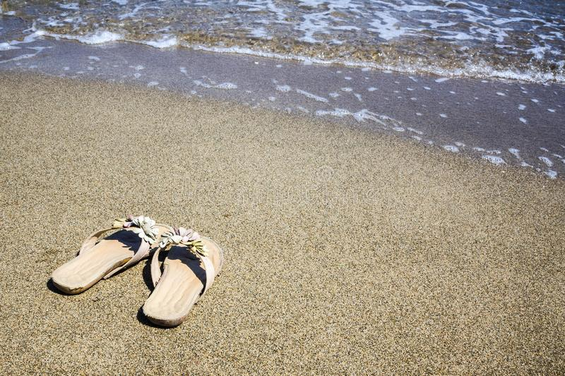 Women\'s slippers on the beach royalty free stock images