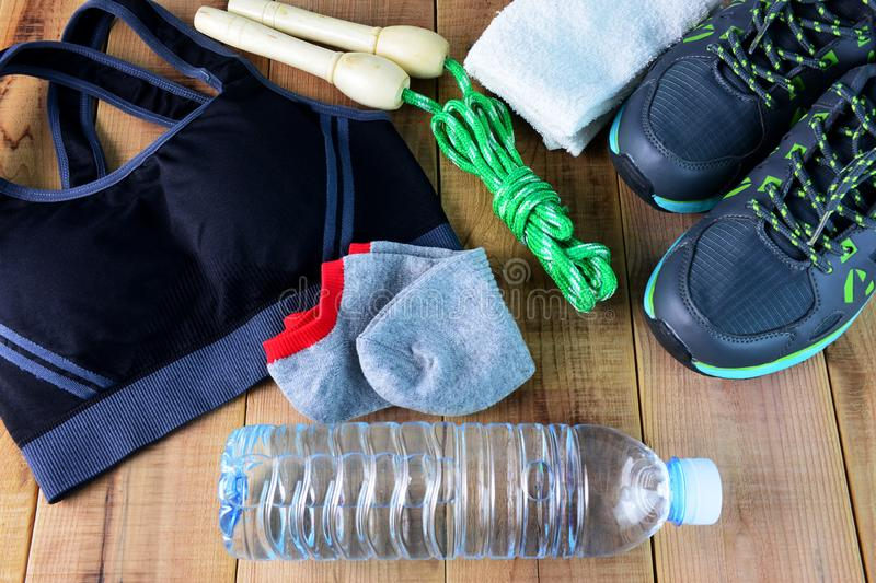Women`s sport bra and shoes, towel, sock, skipping rope, bottle of water on wooden. stock image