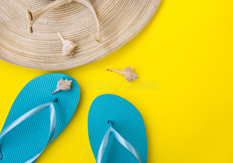 Women`s straw hat, blue slippers, sea shells, nectarine on yellow background, beach vacation, seaside, fashion royalty free stock image