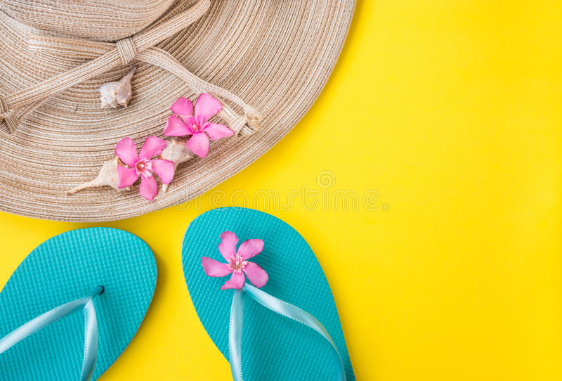 Women`s straw hat, pink tropical flowers, blue slippers, sea shells, on yellow background, beach vacation royalty free stock photos