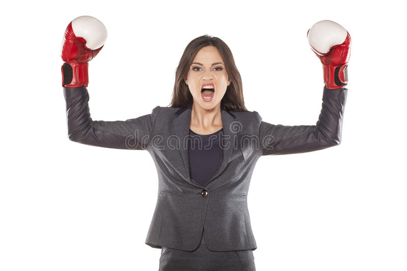 Women's success in business. Angry business woman with boxing gloves in winning position royalty free stock images