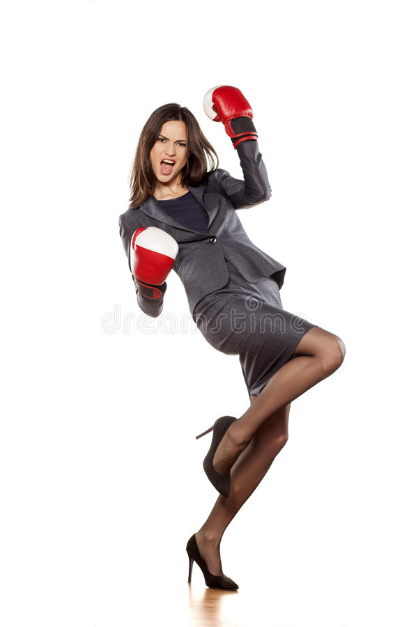 Women's success in business. Happy business woman with boxing gloves in winning position royalty free stock photos