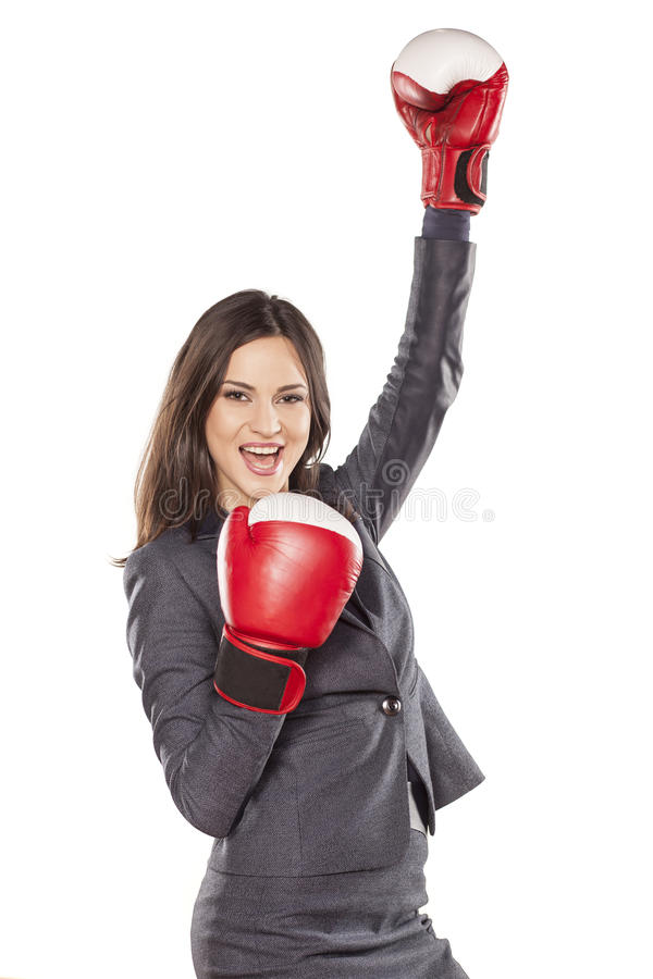 Women's success in business. Happy business woman with boxing gloves in winning position royalty free stock photography