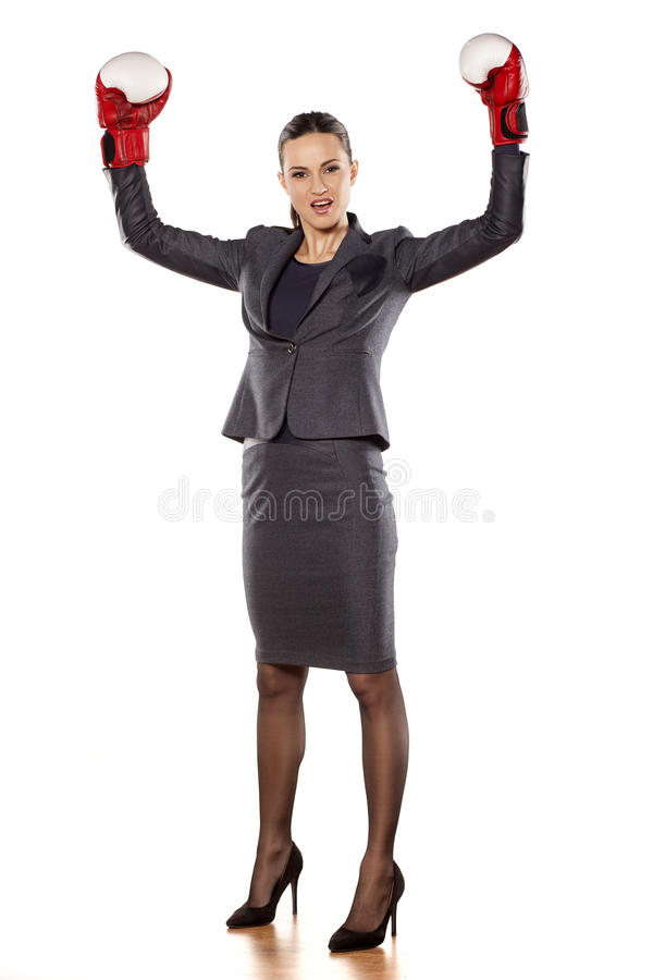 Women's success in business. Happy business woman with boxing gloves in winning position royalty free stock images