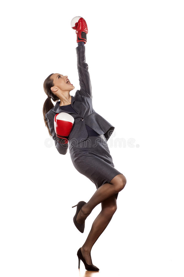 Women's success in business. Happy business woman with boxing gloves in winning position stock images
