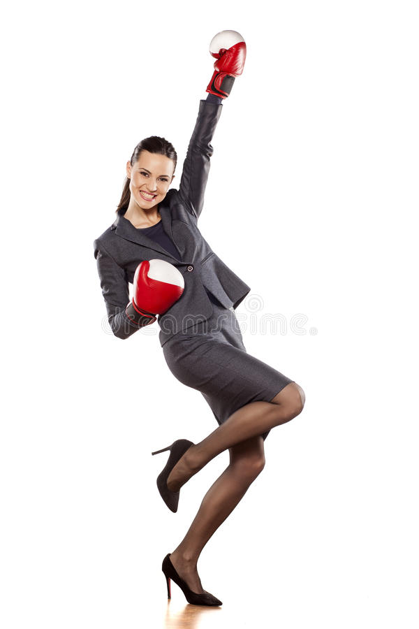Women's success in business. Happy business woman with boxing gloves in winning position royalty free stock image