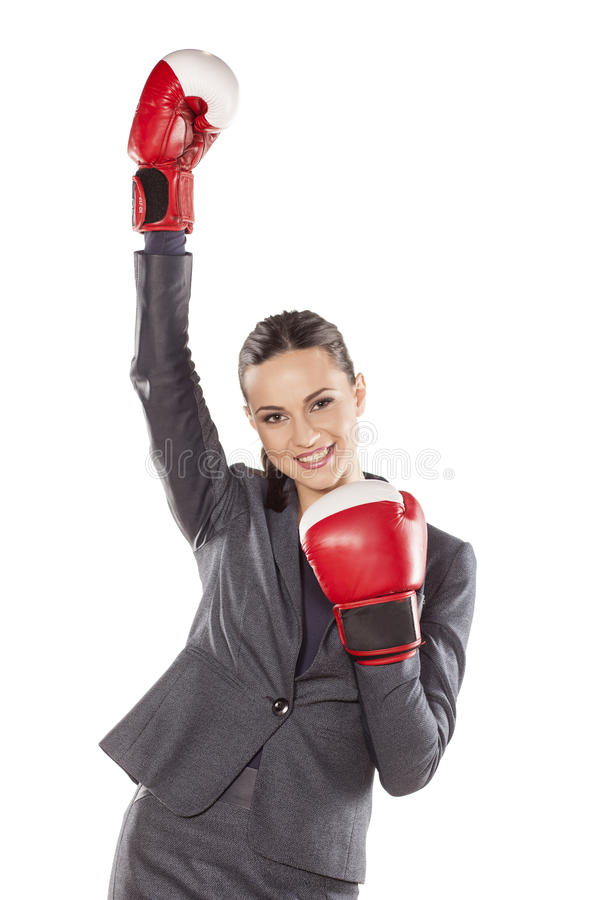 Women's success in business. Happy business woman with boxing gloves in winning position stock photo