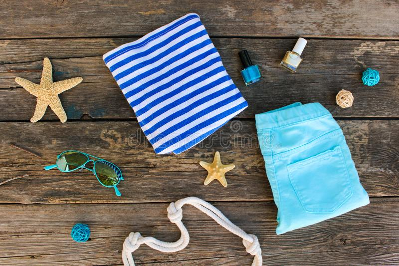Women`s summer clothes and accessories on old wooden background. royalty free stock photos