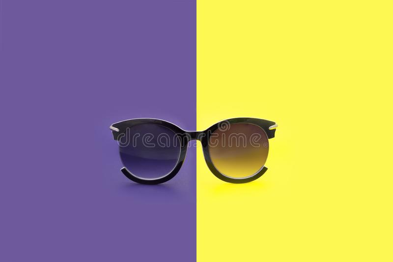 Women`s Sunglasses. Points are located frontally. On a purple-yellow background royalty free stock photography