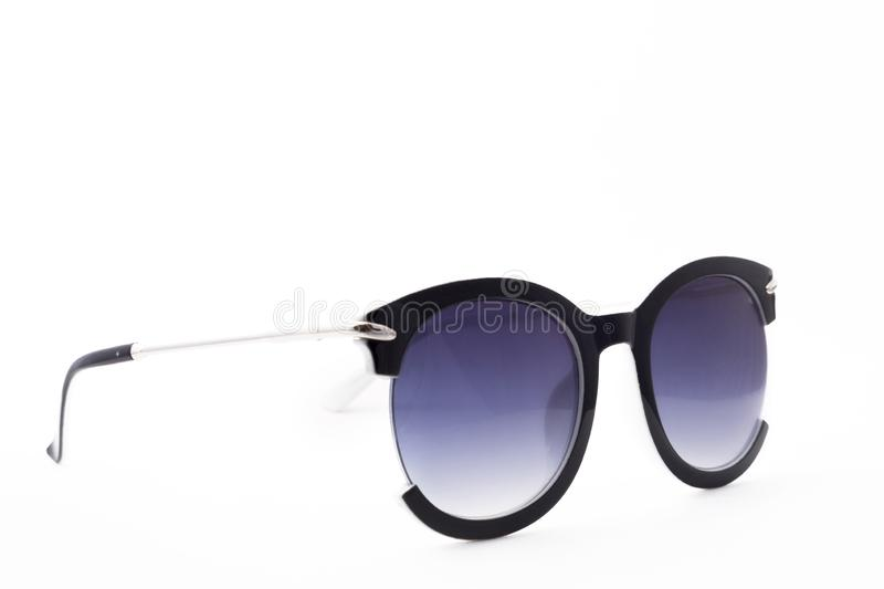 Women`s sunglasses with purple tint stand frontally isolated on a white background with a shadow. Glasses rotated to the right royalty free stock photo