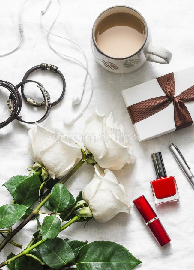 Women`s table beautiful background. Bouquet of roses, gift box, leather bracelets, lipstick, headphones, coffee on a light backgr stock photography