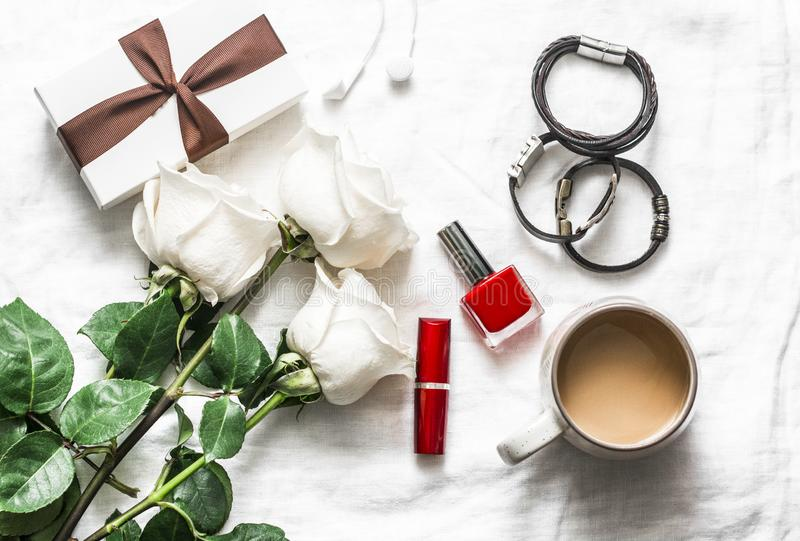 Women`s table beautiful background. Bouquet of roses, gift box, leather bracelets, lipstick, headphones, coffee on a light backgro royalty free stock photography