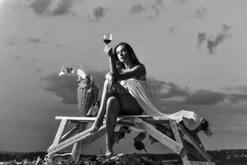 Women`s tenderness. pretty woman with wine over sky stock image