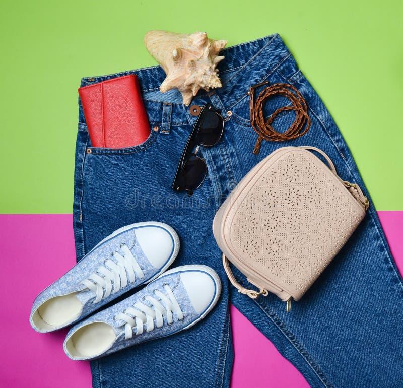 Women& x27; s-tillbehören ligger på klassisk jeans med överdrivna gymnastikskor för en midja, börs, hänger löst, kuter på en rosa royaltyfri fotografi