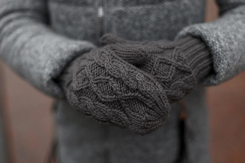 Women`s Vintage knitted winter warm gray mittens on the hands. Photo Closeup. Women`s Vintage knitted winter warm gray mittens on the hands. Photo Closeup stock photography