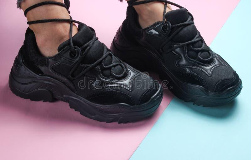 Women& x27; s voeten in in zwarte tennisschoenen stock afbeeldingen