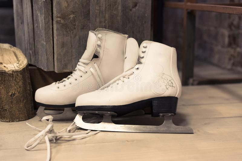 Women`s white skates are on the floor. feminine. to skate. winter sport royalty free stock photo
