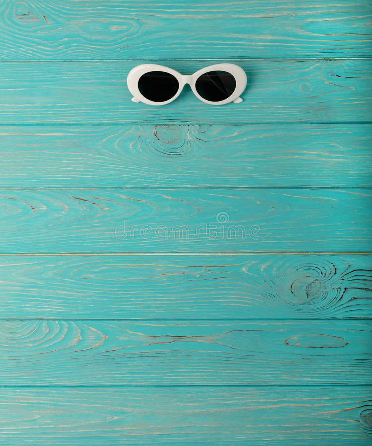 Women`s white sun glasses on a blue wooden background. royalty free stock photos