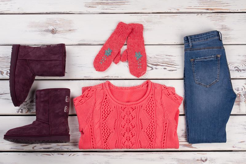 Women`s winter outfit on showcase. Combination of jeans with handmade knitted clothes and boots stock photos