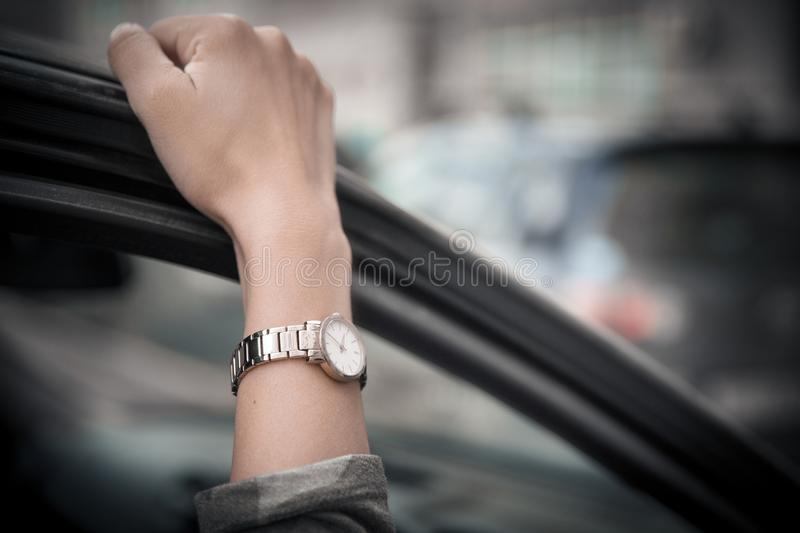 Women`s wristwatch on the girl`s hand. Girl in a hurry, standing in a traffic jam. Time is money. Man loses time stock photos