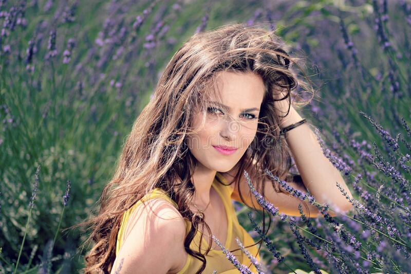 Women's Yellow Tank Top Holding Her Brown Curly Hair While Sitting on a Purple Flower royalty free stock photos