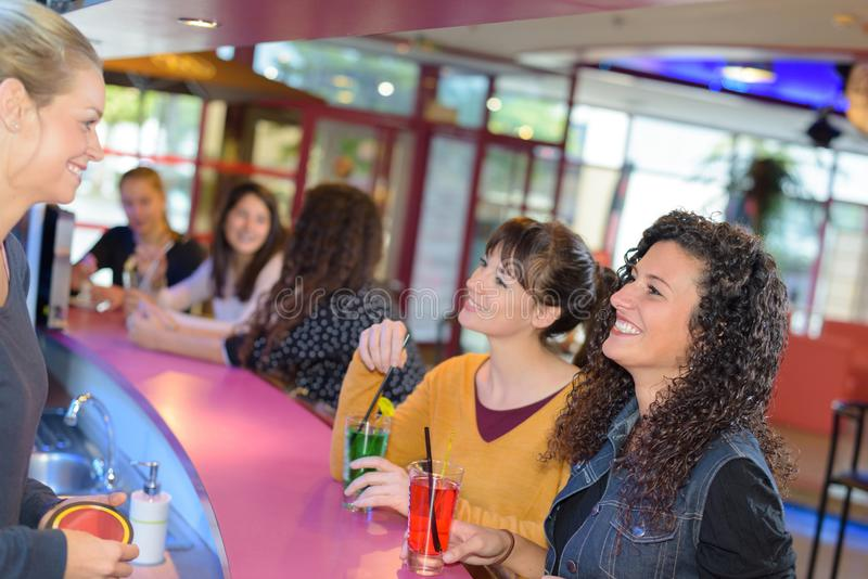 Women sat and bar talking to barmaid royalty free stock image