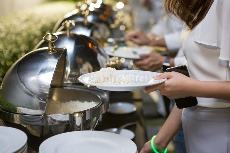 Women are scooping food from chafing dishes. On the table at the luxury banquet stock images