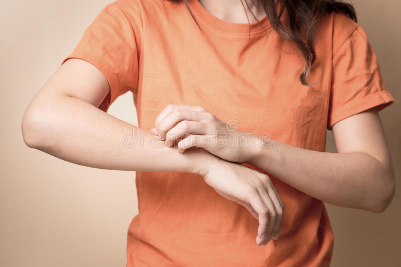 Women scratch itchy arm, Women scratch itchy arm with hand. Women scratch itchy arm with hand stock photo