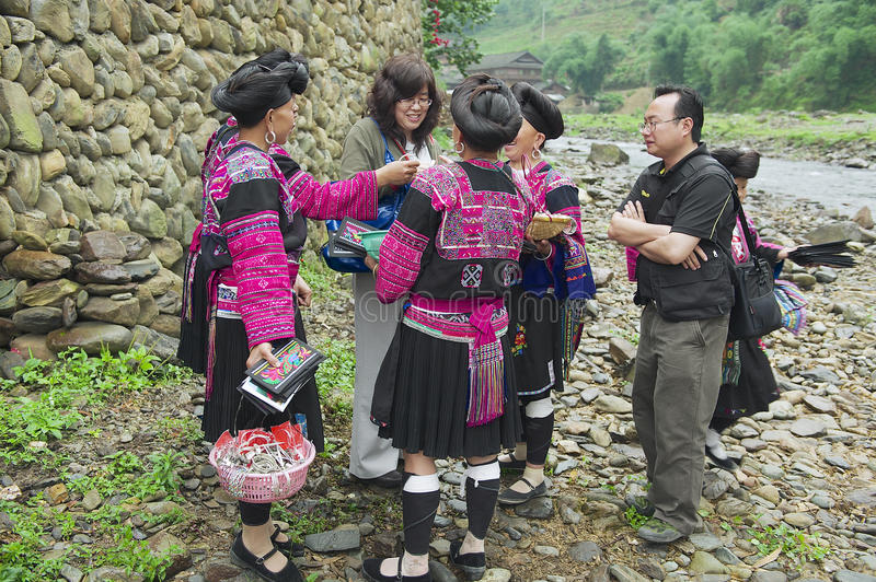 Women sell souvenirs to a tourist in Longji, China. stock photography
