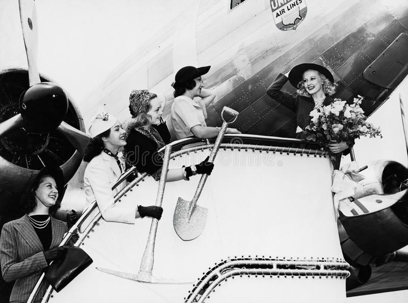 Women sending off friend boarding plane stock photos