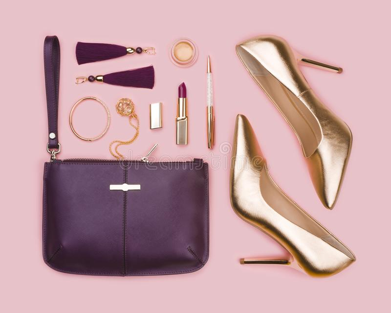 Women set of gold purple fashion accessories on pink background stock images