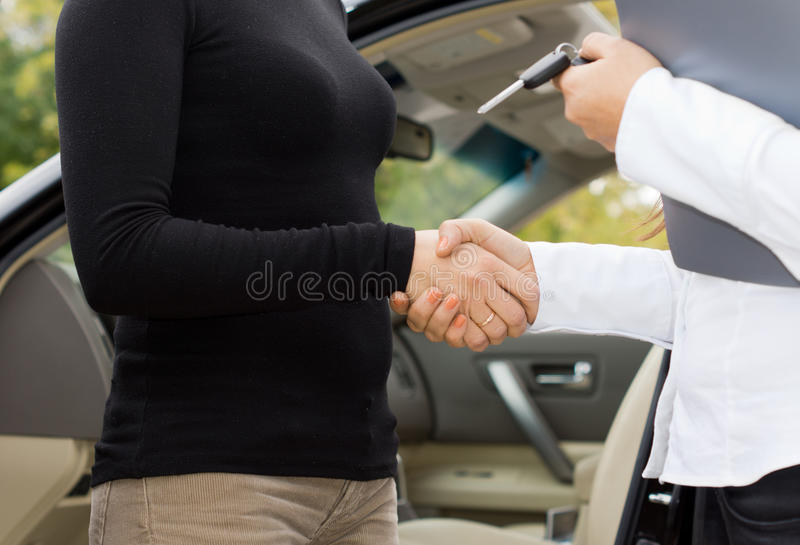 Women shaking hands on a car purchase. Close up view of the hands of two women shaking hands on a car purchase with one holding the contract and keys stock photography