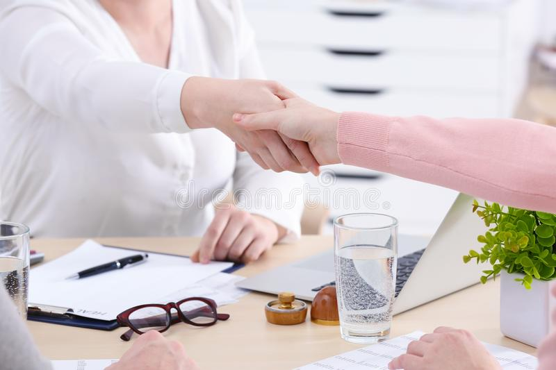 Women shaking hands sitting at workplace. In office royalty free stock image