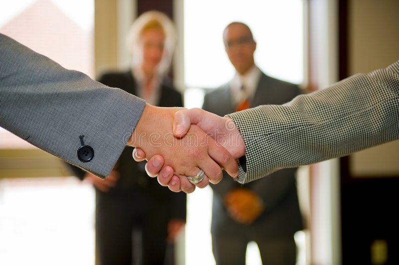Women Shaking Hands to Confirm Agreement. Women shaking hands in the foreground with team members looking on stock photography