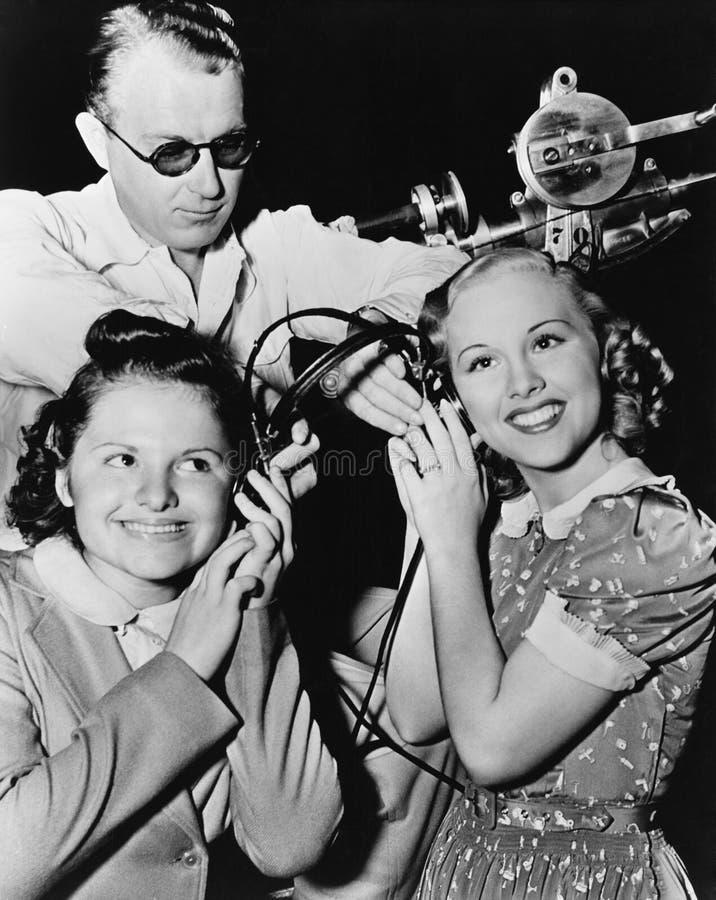 Women sharing pair of headphones stock photos