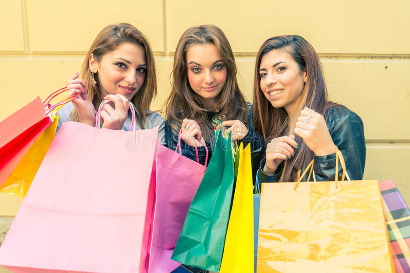 Women and shopping. Women with shopping bags - Portrait of three pretty girls posing in front of camera stock photo