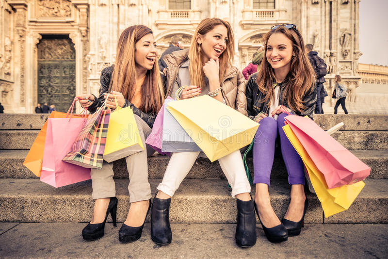 Women and shopping. Women with shopping bags - Portrait of three pretty girls sitting on a staircase while laughing and talking royalty free stock image