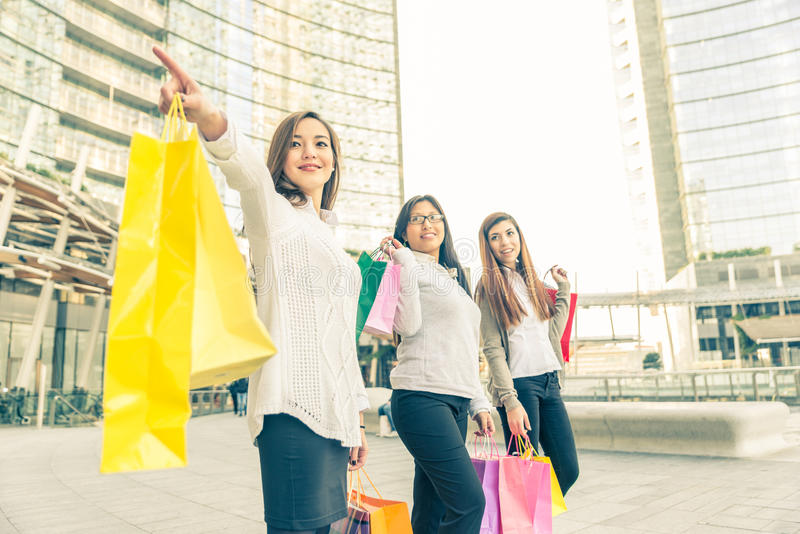 Women and shopping. Women with shopping bags - Portrait of three pretty girls walking and looking at shops royalty free stock photos