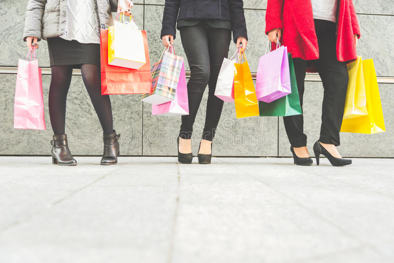Women and shopping. Women with high heels and shopping bags - Three girls standing and chatting after buying presents royalty free stock photos